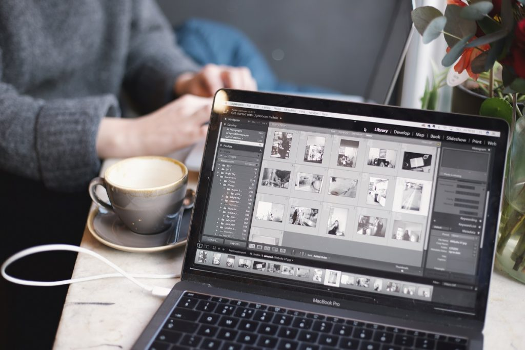Editing photos using laptop with a cup of coffee on the side